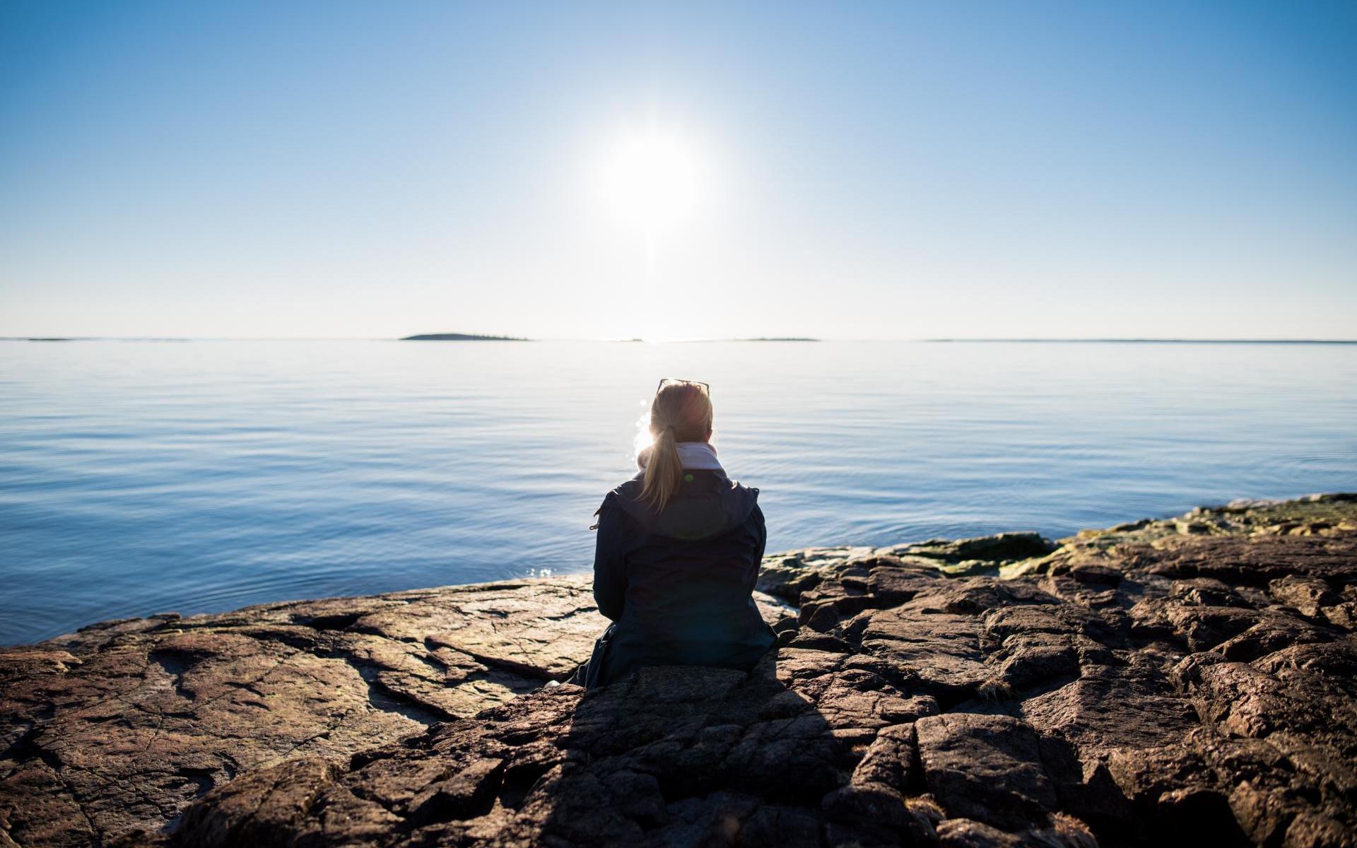 Kvinna njuter av solvarma klippor och ser ut över vattnet